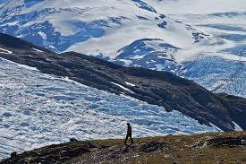 A person walking along the base of the Woverine Glacier.