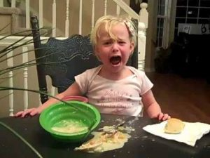 a little girl crying over spilled food.